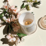 Glossy White Large French Gala Candle Jar in the centre of the picture showing 'How It Works'. This being the first step, it shows the candle burning its way down to half way, ready to discover your sparkle within, surrounded by pretty flowers.