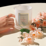 Glossy White Large French Gala Candle Jar in the centre of the picture showing 'How It Works'. This being the final step, it shows a glamorous sparkling ring on a female finger surrounded by pretty flowers.