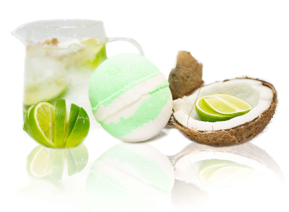 Green & White Coconut & Lime Bath Bomb sitting in the centre of the screen surrounded with freshly cut zesty lime and coconut. showing you the scent in in a picture. Wait until you smell it for yourself.