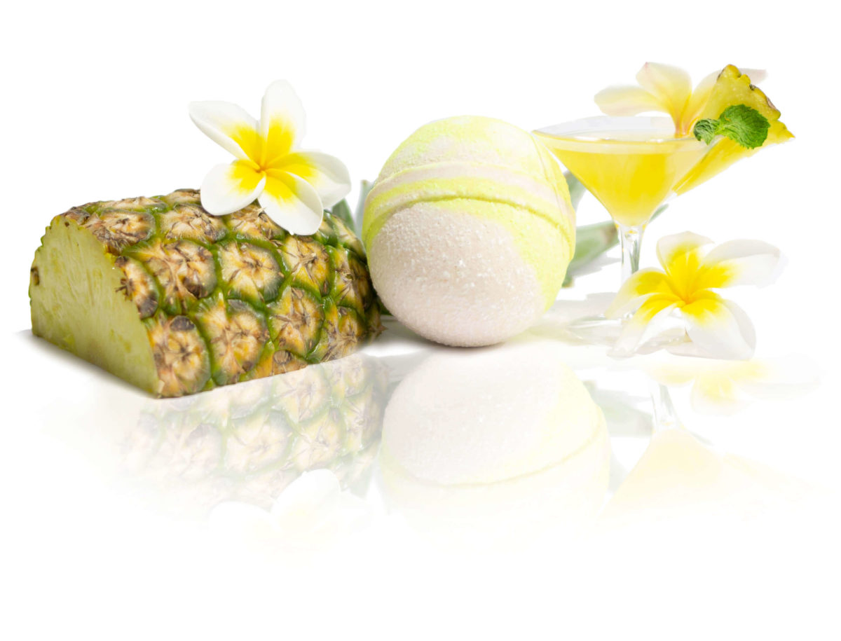 Yellow & White Bath Bomb sitting in the centre of the screen surrounded with yellow pineapple, cocktails & Frangipani flowers showing you the scent in in a picture. Wait until you smell it for yourself.