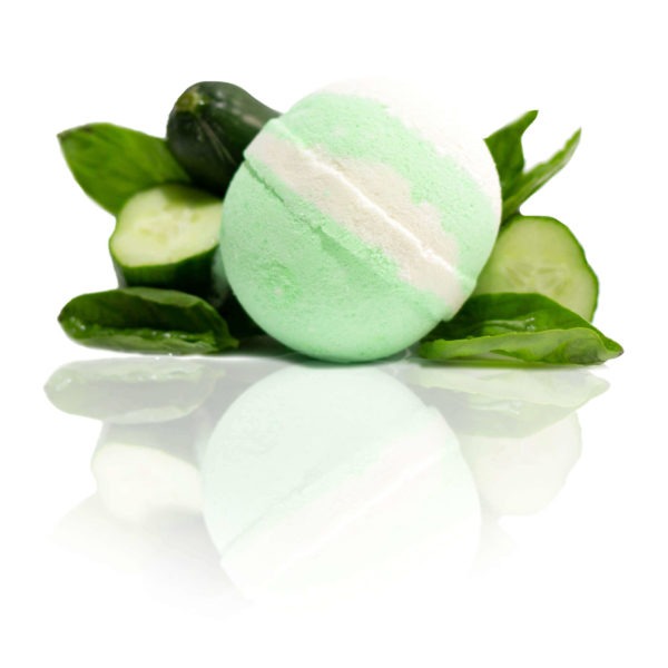 Basil & Cucumber Bath Bomb surrounded by fresh basil & Cucumbers with a glossy reflective surrounding.