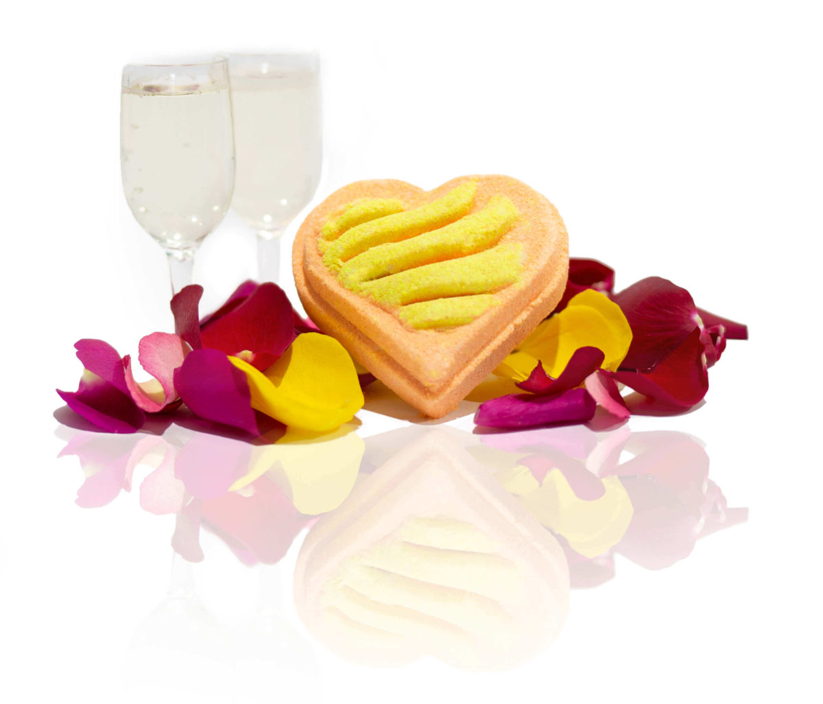Gold & Orange love heart bath bomb with a wavy pattern on top in the centre of the screen surrounded by rose petals and champagne.