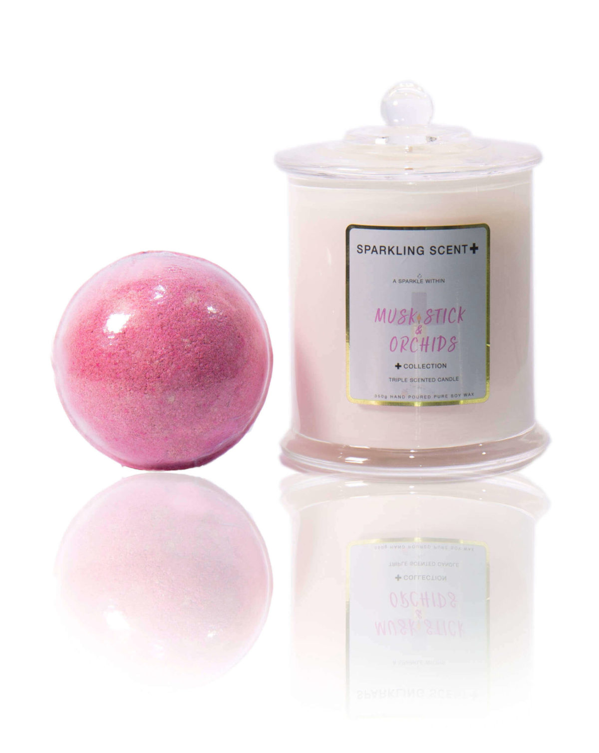 Musk Sticks gift set in the centre of the screen. A bright mica pink Bomb bomb and a Glossy White Elegant French Gala candle.