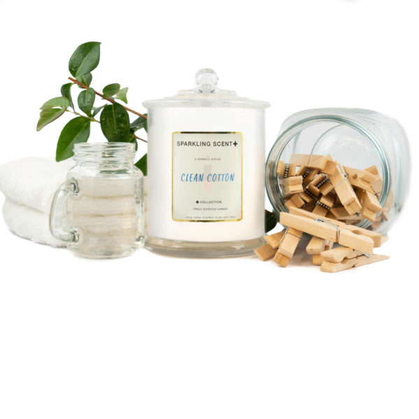 Glossy white shining French Gala Candle with a gold and white sticker. Surrounded by what you can imagine from the scent. Fresh white towels, wooden pegs in a glass jar and vibrant green leaves.