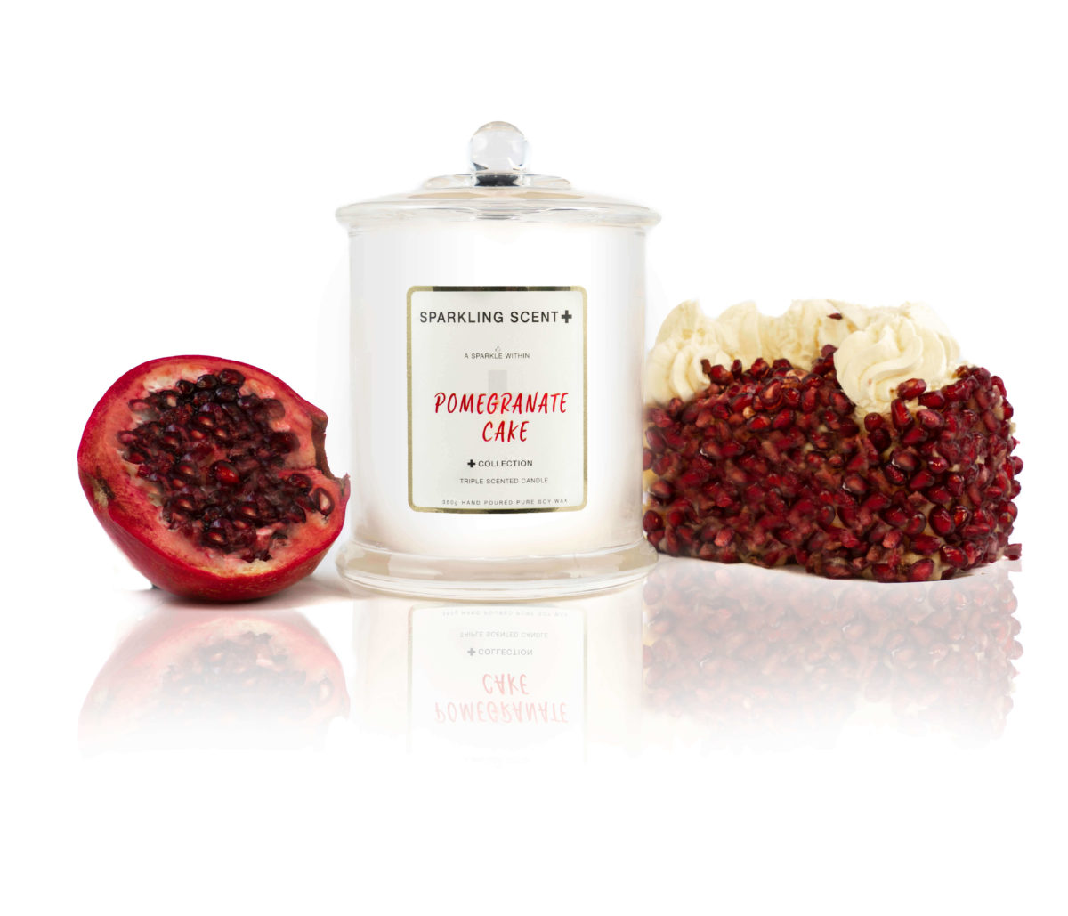 Glossy white shining French Gala Candle with a gold and white sticker. Surrounded by what you can imagine from the scent. Pomegranate creamy cake as well as a fresh pomegranate cut in half.