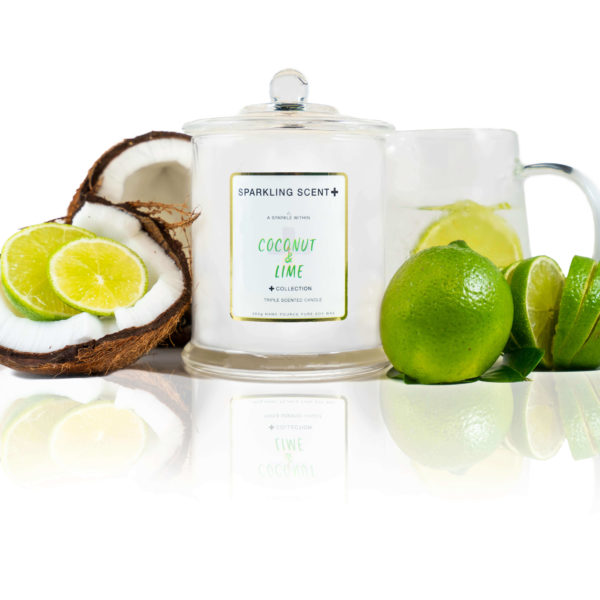Glossy white shining French Gala Candle with a gold and white sticker. Surrounded with what you can imagine from the scent, cracked in half coconuts, sliced up an full cold dripping limes, ice cold water glass jars with juiced lime inside and topped off with lime leaves.
