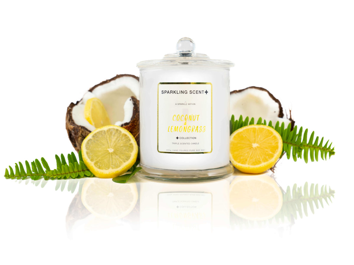 Glossy white shining French Gala Candle with a gold and white sticker. Surrounded with what you can imagine from the scent, cracked in half coconut, dripping lemons and lemon grass.