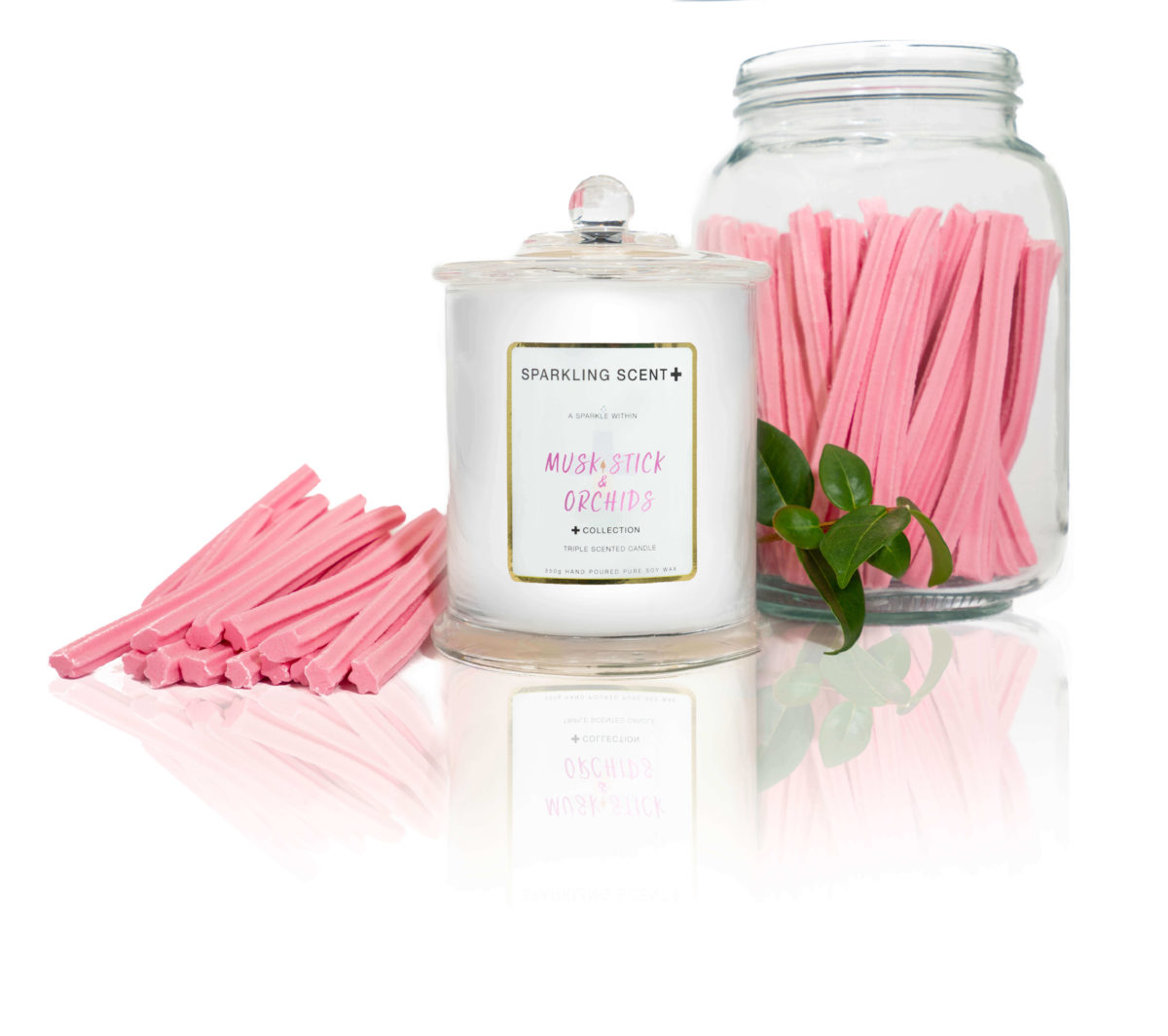 Glossy white shining French Gala Candle with a gold and white sticker. Surrounded with what you can imagine from the scent, pink Musk Sticks-in a jar swell as Orchids.